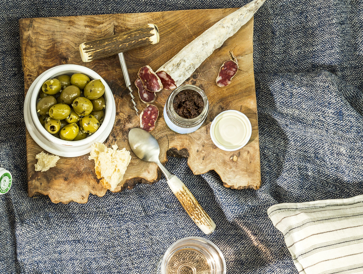 Tapenade, olives, and saucisson, on cutting board at picnic.